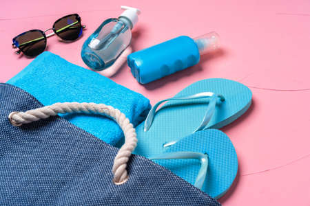Beach essentials and blue beach bag on pink background