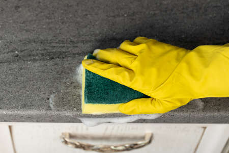 Womans hands in yellow gloves cleaning counter top in kitchen