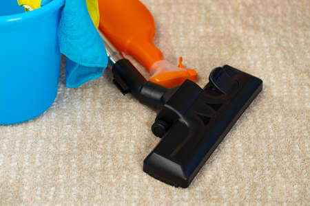 Red vacuum cleaner and plastic bucket with liquid detergents on beige carpet