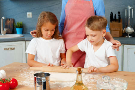 Young blonde woman, mother and her kids having fun while cooking dough 版權商用圖片