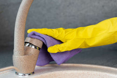 Hands in yellow gloves cleaning a sink with a sponge