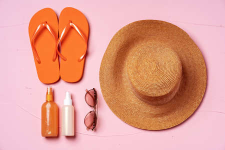 Suntan oil spray bottles and straw hat on pink background 版權商用圖片