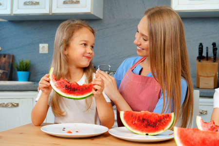 Mother and daughter eating watermelon at home