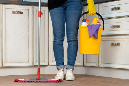 Woman washing floor with mop in kitchen