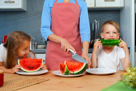 Sweet family, mother and her kids eating watermelon in their kitchen having fun