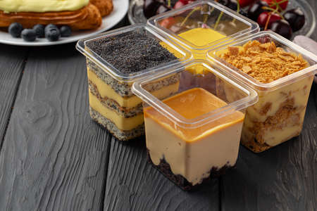 Mousse dessert in plastic transparent box on black wooden table 版權商用圖片