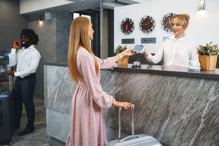 Young attractive woman with packed suitcase standing in hotel lobby Standard-Bild