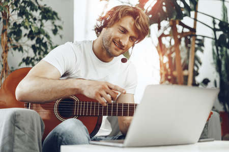 Young man watching guitar tutorial on his laptop