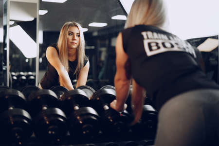 Back view of a woman training her hands with a dumbbell in a gym