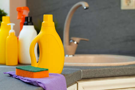 Household chemicals product bottles standing near the kitchen sink Foto de archivo