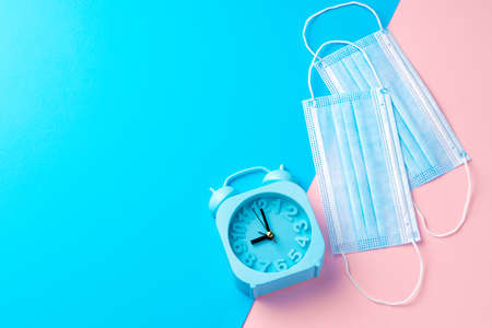 Blue alarm clock and medical face mask