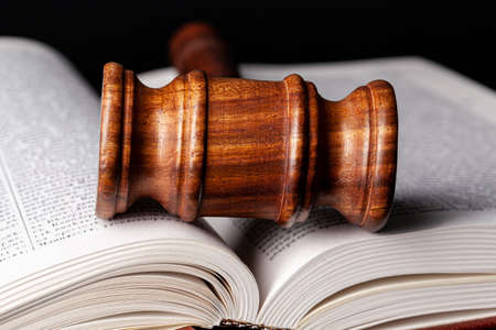 Wooden gavel and juridical books close up