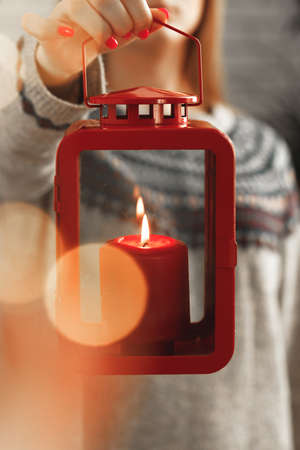 Red burning Christmas candle in female hands