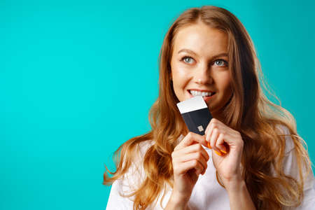 Smiling young woman biting a credit card within temptation of shopping