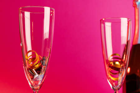 Champagne glasses with party tinsel on bright background Фото со стока