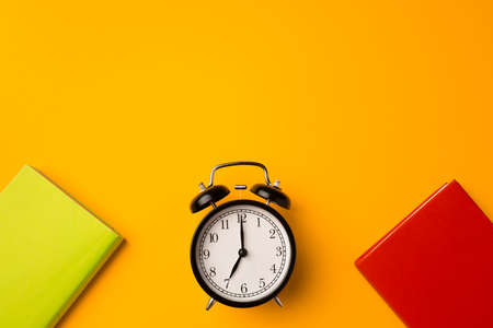 Three color hardcover notepads and alarm clock on yellow background