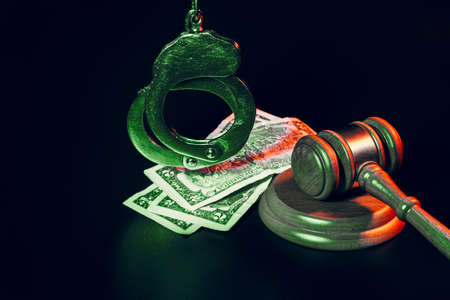 Bribe concept. Dollar banknotes, handcuffs and gavel on dark black table Banque d'images