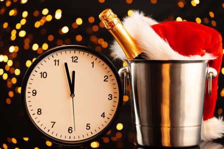 New Year eve concept with alarm clock against blurred garland Imagens