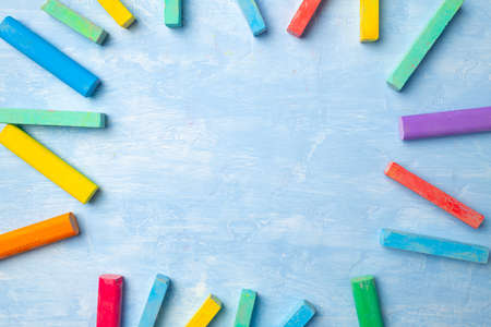 Colorful chalks on blue background with copy space for text