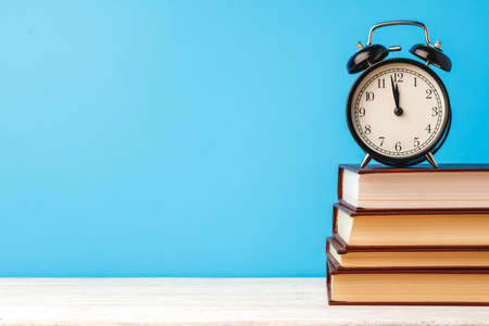 Books and alarm clock on table, education concept Imagens