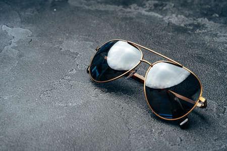 New dark aviator glasses on grey concrete background Foto de archivo