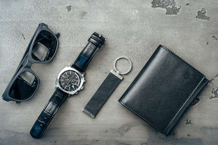 Male accessories: wallet, watch and sunglasses on dark grey surface Stockfoto