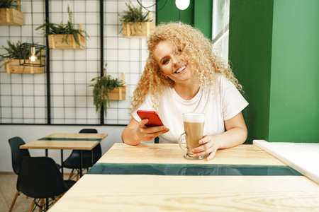Beautiful curly blonde woman taking selfie while sitting at the table in coffee shop