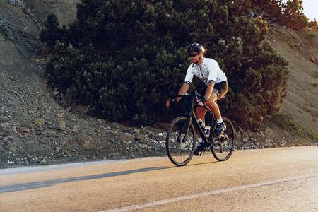 Professional cyclist on a mountain road at sunrise Foto de archivo