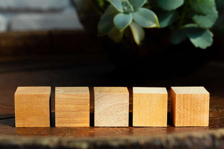Groupped wooden square blocks on dark wooden table