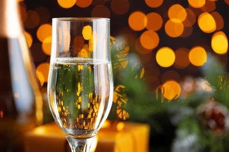 Champagne glass on blurred garland lights background