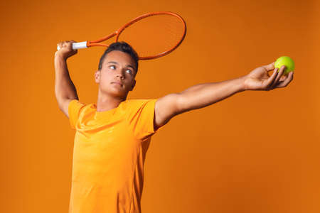 Studio shot of a young tennis player holding racket against orange background