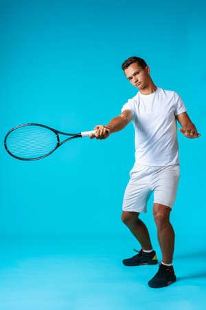 Full length studio portrait of a tennis player man on blue background 写真素材