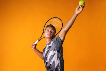 Portrait of a young man tennis player on orange background 写真素材