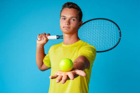 Young man tennis player in sportswear posing against blue background