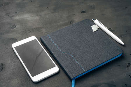 Blue notepad, smartphone and pen on dark grey table