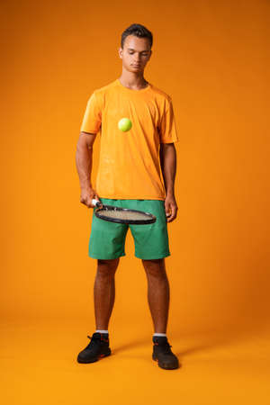 Full-length portrait of a tennis player man in action against orange background