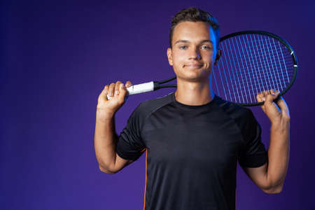 Caucasian young man tennis player posing with tennis racket against purple background 写真素材