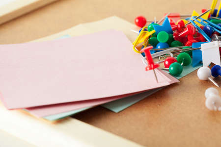 Sticky notes with pushpins and blank space on cork background. School or business concept