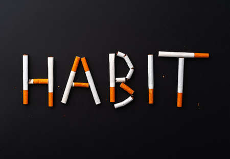 Inscription word HABIT made out of cigarettes top view Фото со стока