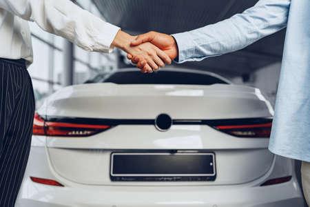 Car seller and buyer handshake at car dealership against a new car