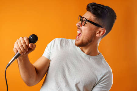 Hispanic young handsome man singing with joy in microphone