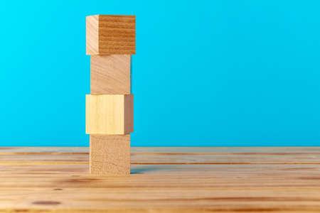 Stacked wooden blocks on wooden desk against blue background