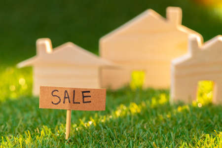 Wooden toy house on grass with sale sign