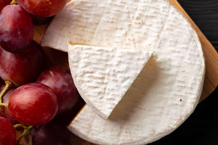 Close up photo of cut cheese and grapes