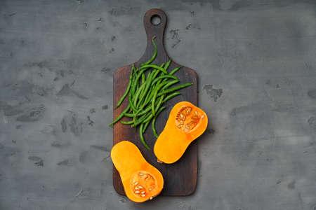Raw orange pumpkin and wooden cutting board