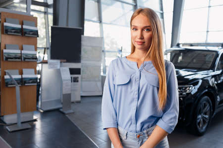 Young beautiful car saleswoman standing in car showroom