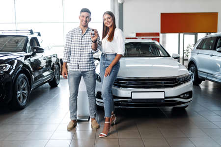 Young happy couple just bought a new car in a dealership