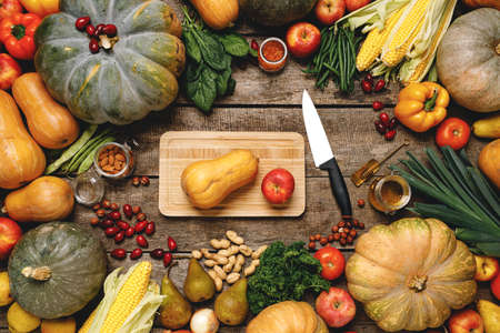 Wooden cutting board with autumn vegetables on wooden table