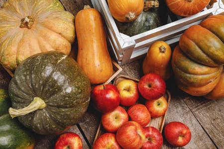 Pumpkins and red apples on wooden background Reklamní fotografie