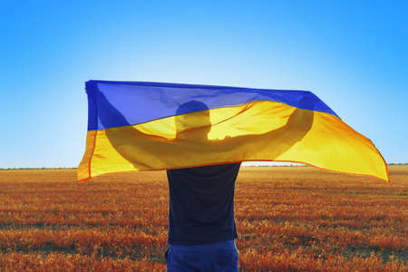 Man with a flag of Ukraine standing in field